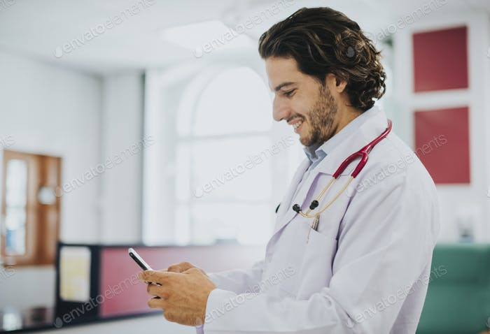 Male doctor using his smartphone