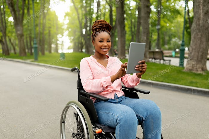 Happy impaired young woman in wheelchair using tablet computer for online communication outdoors