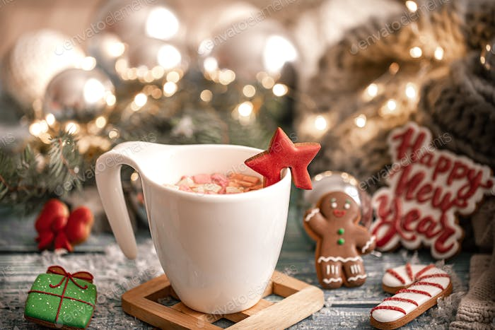 Christmas composition with white cup with hot drink with marshmallows on cozy background close up.