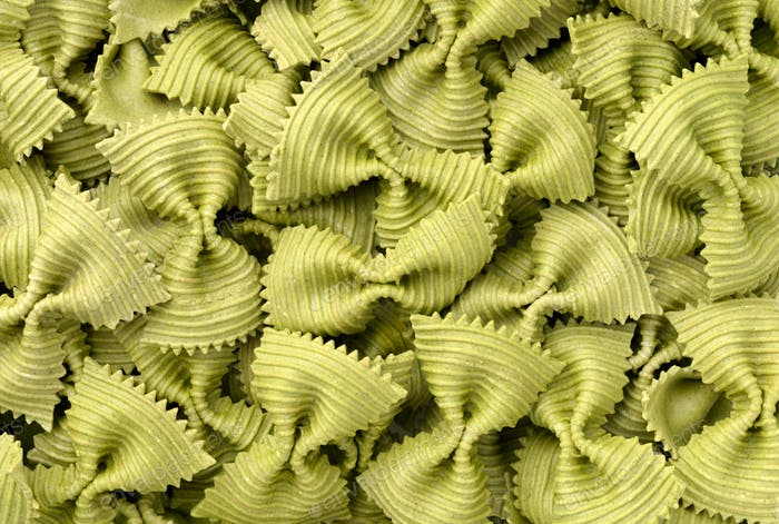 Uncooked green spinach farfalle pasta background