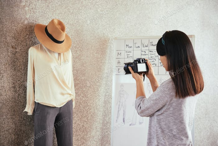 Anonymous tailor taking picture of outfit