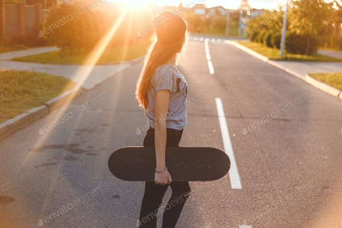 Beautiful and fashion young woman posing with a skateboard on the street