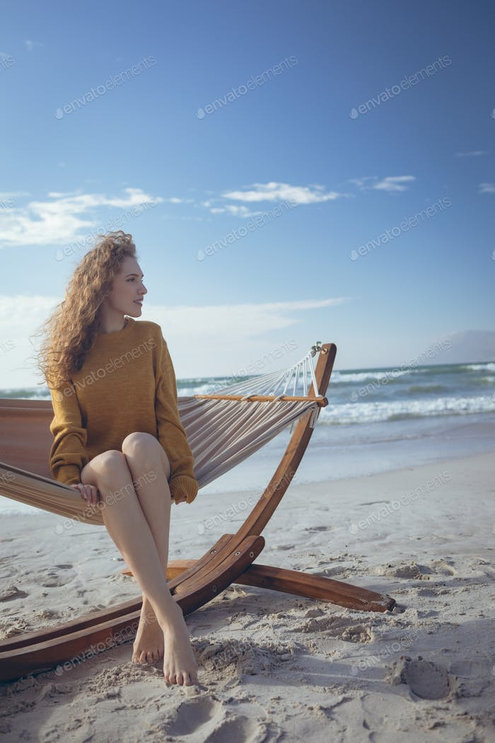 Young beautiful woman sitting on hammock with leg crossed at beach on a sunny day