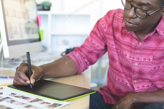 Front view of young African-American graphic designer working on graphic tablet at desk in office