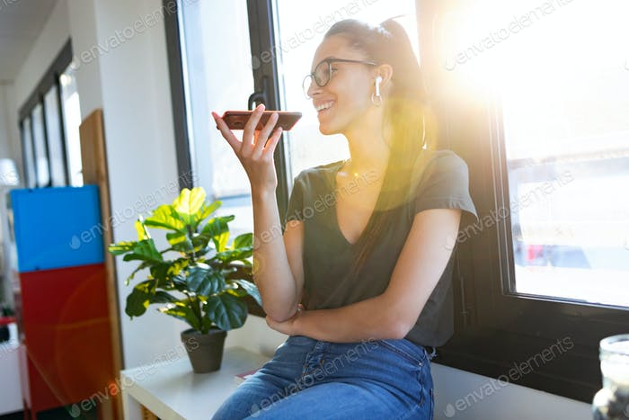 Lächelnd junge Geschäftsfrau mit ihren freien Händen, um einen Anruf mit dem Handy zu machen