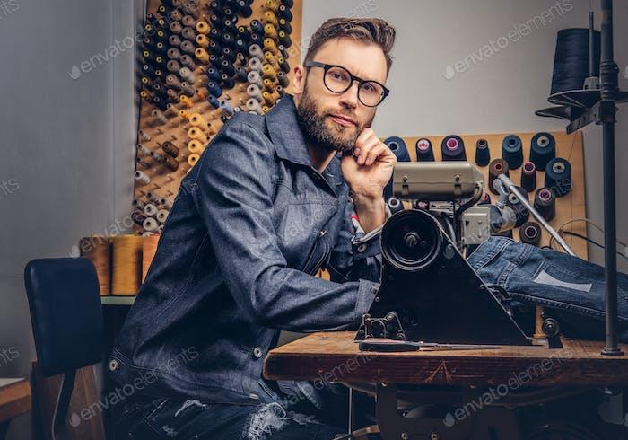 Bärtige Modedesignerin in einer Nähwerkstatt