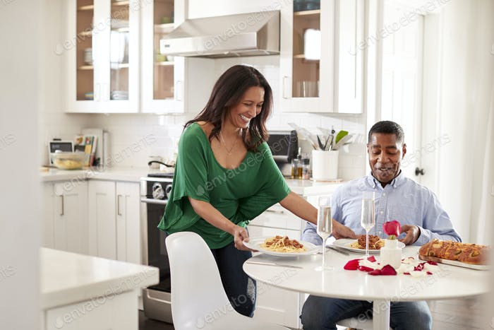 Middle aged mixed race woman woman serving her partner a romantic meal