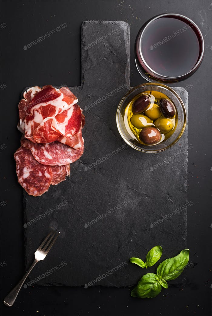 Glass of red wine, meat appetizer, olives and basil on black  slate stone board over dark background