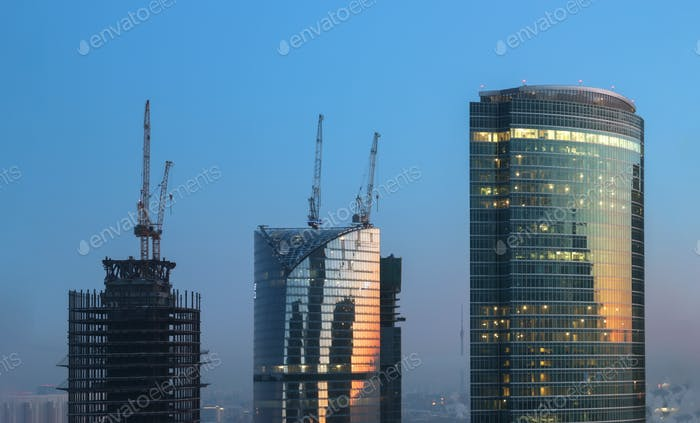 Tops of the three towers of different heights of skyscrapers