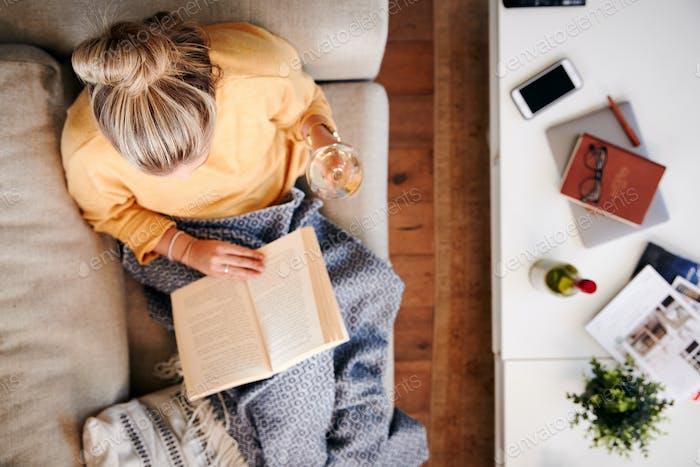 Overhead Shot Blick nach unten auf Frau zu Hause liegend auf Lesen Buch und Wein trinken