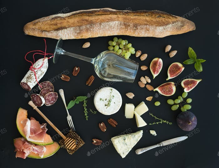 Wine and snack set. Baguette, glass of white, figs, grapes, nuts