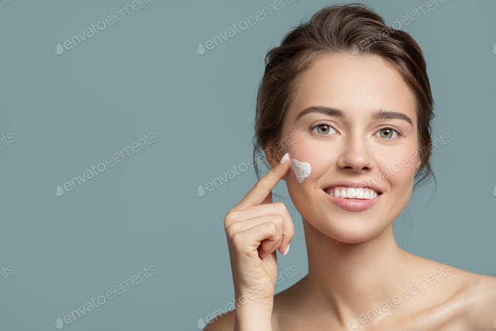 Portrait Of Beautiful Woman Applying Cream On Her Face.