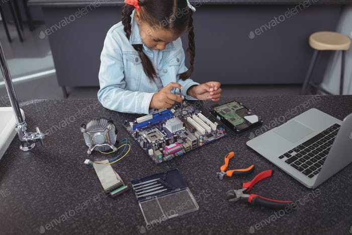 High angle view of concentrated elementary girl assembling circuit board
