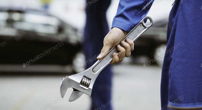 Mechanic man hand holding wrench in auto repair shop