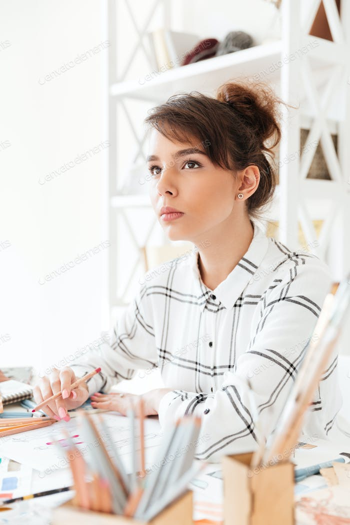 Young attractive female designer creating new clothes