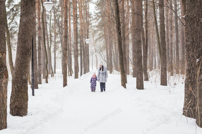 Motherhood, children and nature concept - Attractive young woman and adorable child walking in park