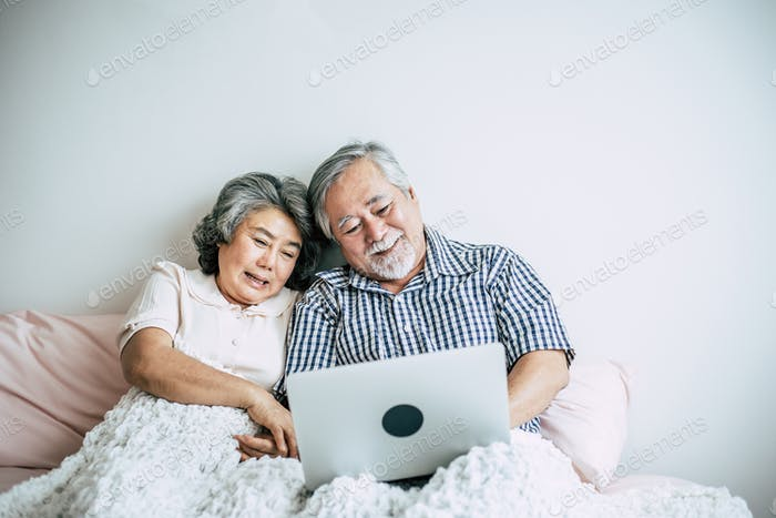 Elderly couples talking and using laptop in bedroom
