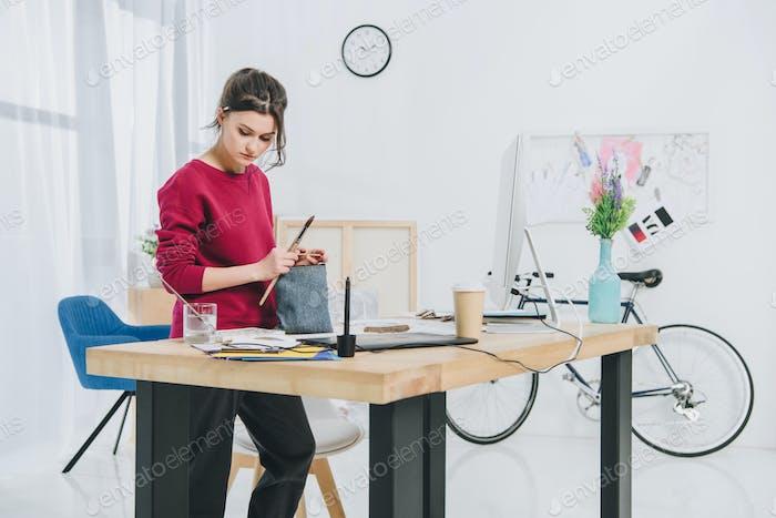 Mujer joven con Ilustraciones por mesa de trabajo con computadora