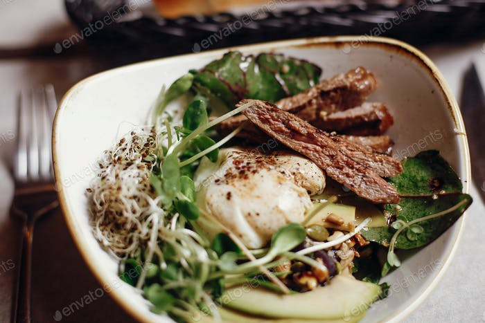 Delicious salad with juicy grill steak, avocado, sprouted greens, leaves, egg pouch, nuts