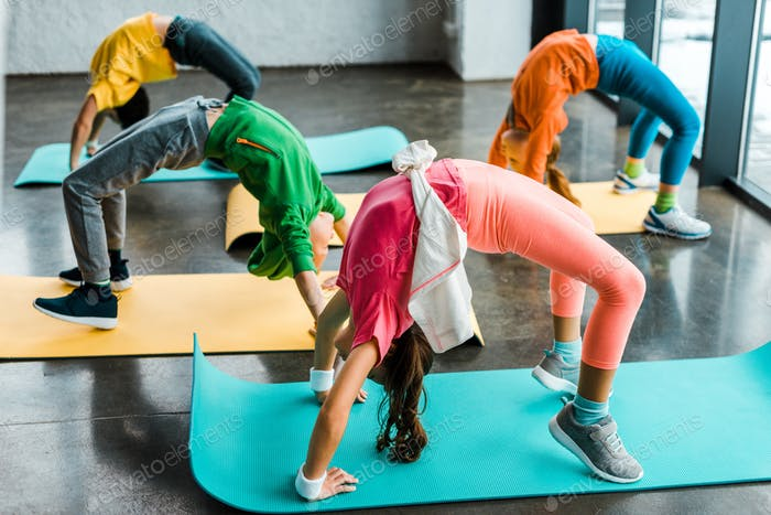 Kids doing gymnastic exercise on fitness mats