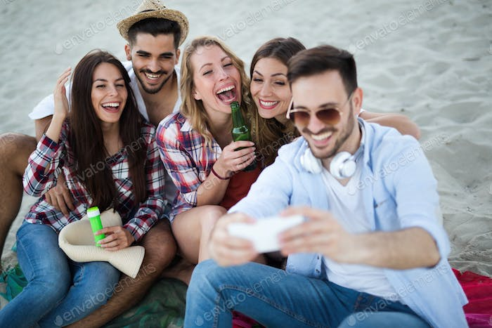 Group of happy friends having fun at beach in summer