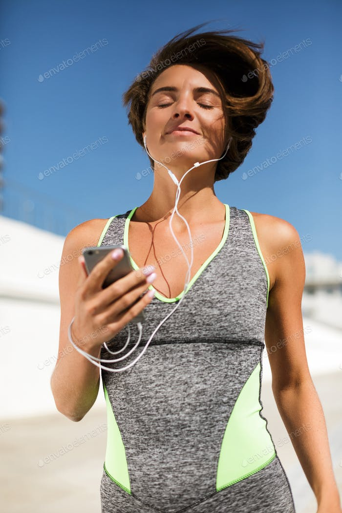 Beautiful smiling woman in modern gray sport suit jogging holding cellphone and earphones dreamily