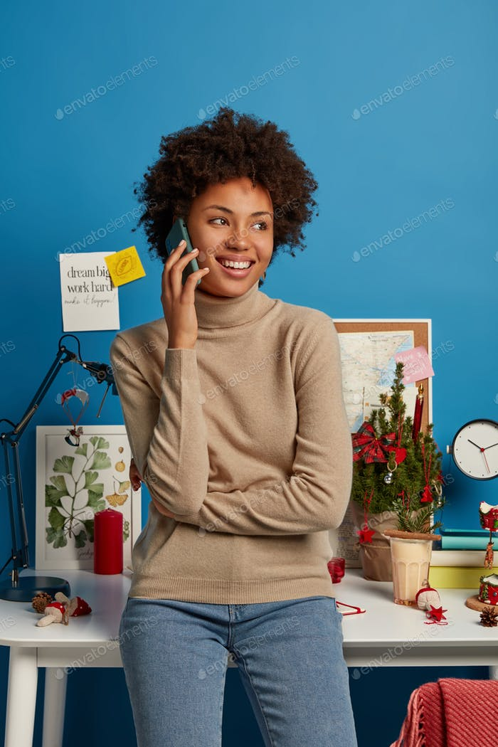 Photo of pleased Afro American freelancer stands in own cabinet at home, has phone conversation, loo