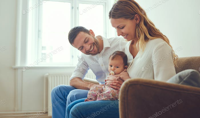 Young couple sitting at home with their cute baby girl