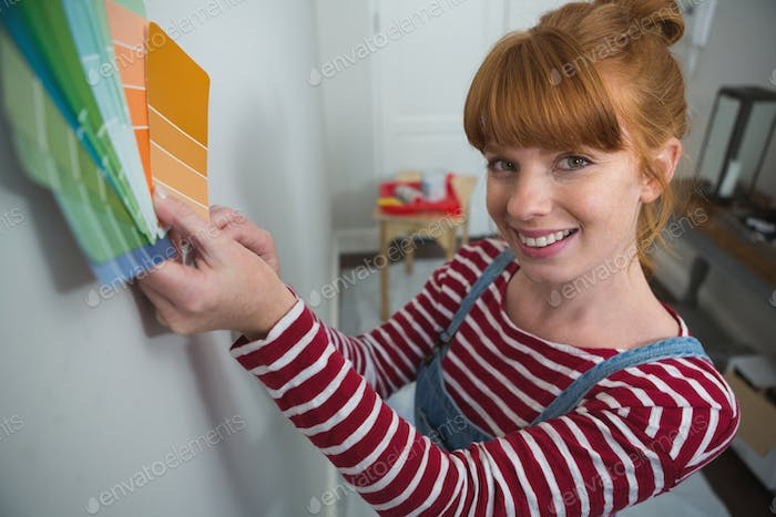 Portrait of female painter matching color shades at home