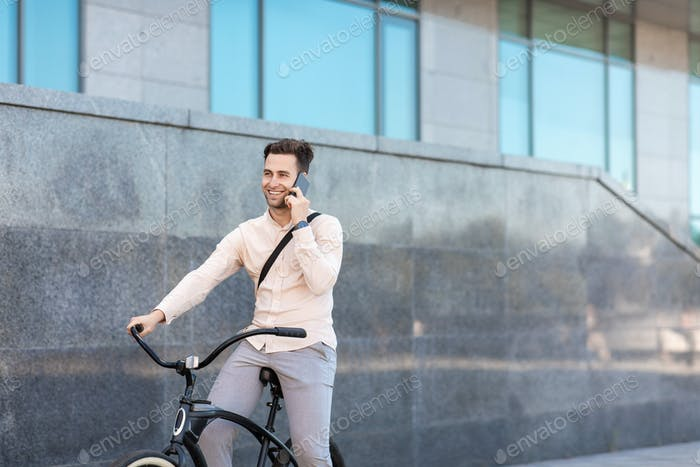 Communication on smartphone during ride. Young businessman with bicycle