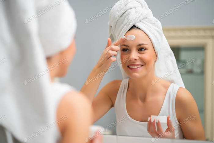 Woman applying moisturizer to her skin