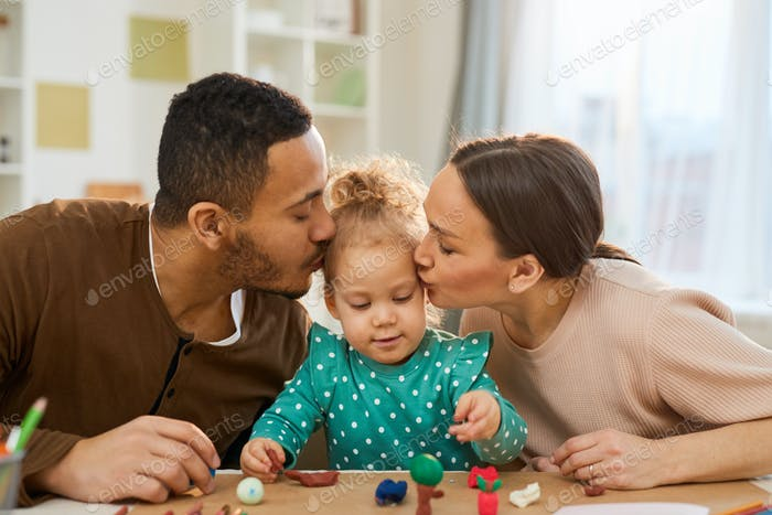 Loving Parents Kissing Child