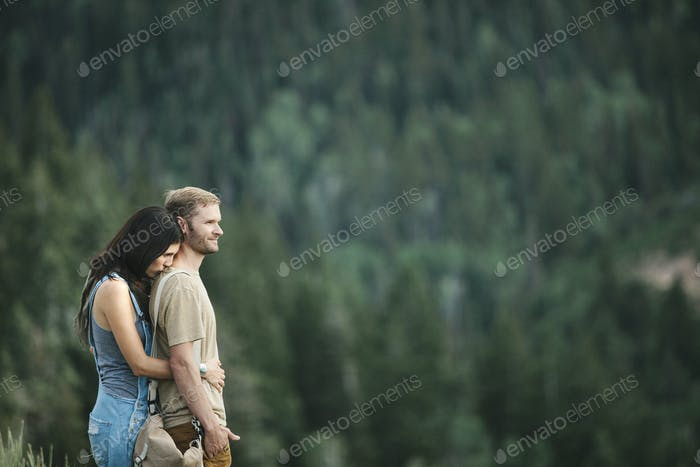 A couple standing embracing in the mountain landscape.