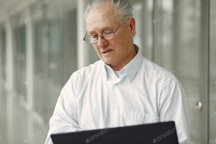 Old man standing in the office with a laptop