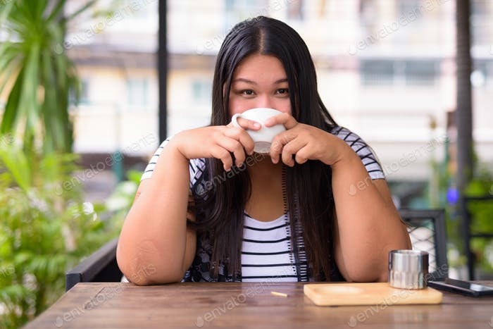 Beautiful overweight Asian woman relaxing at the coffee shop