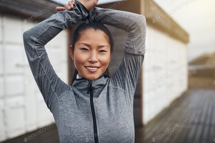 Smiling young Asian woman warming up before an outdoor run