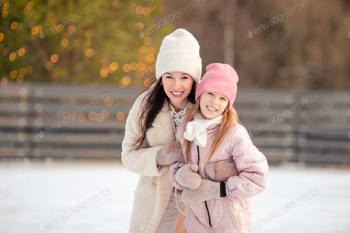 Little adorable girl with her mother skating on ice-rink