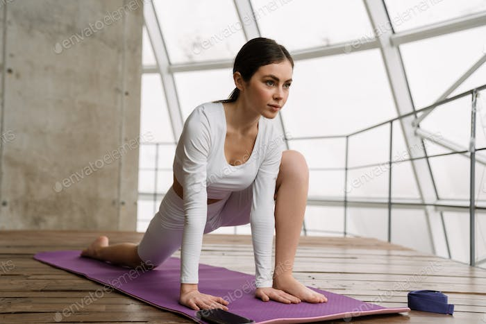 Young white woman doing exercise during yoga practice indoors