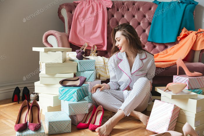 Happy young lady sitting on floor near sofa indoors