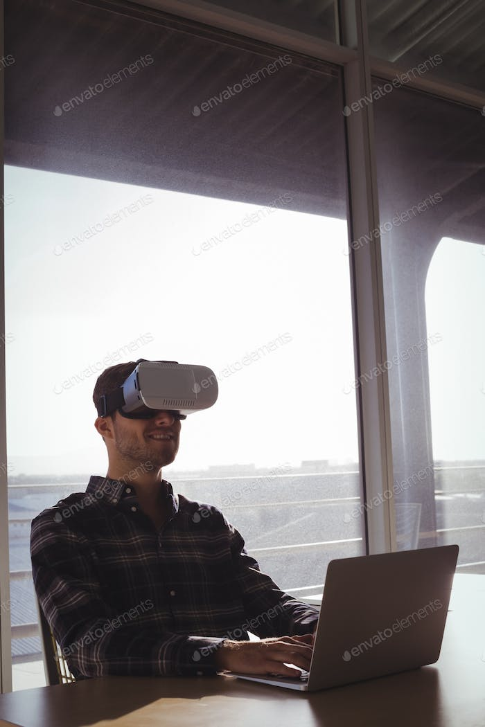 Businessman using virtual reality headset while using laptop in office