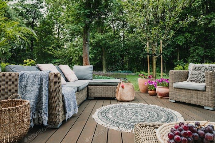 Gartenterrasse dekoriert mit skandinavischem Weidensofa und Couchtisch