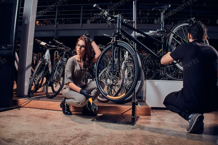Diligent master and his hardworking apprentice are repairing bicycle at workshop