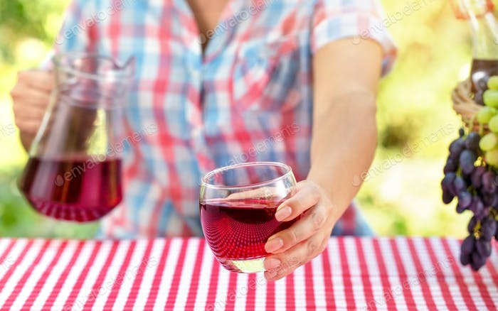 Woman holds out glass of wine or grape juice over table with red tablecloth