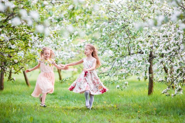 Schöne Mädchen im blühenden Apfelbaumgarten genießen warmen Frühlingstag