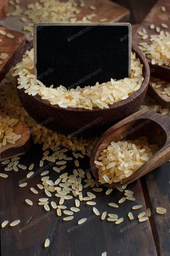 Parboiled rice with a wooden spoon and small chalkboard close up
