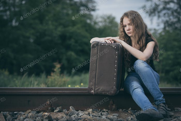 Portrait of young sad ten girl standing with suitcase outdoors a