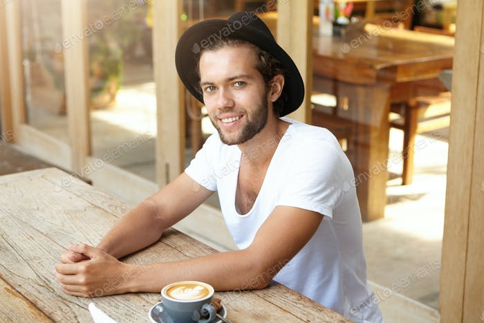 People, lifestyle and leisure. Indoor portrait of handsome young hipster in stylish black hat sittin