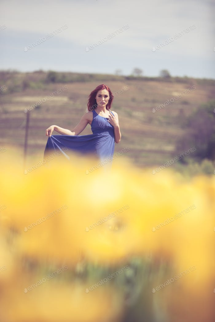 Beautiful woman in flower field in sunny day