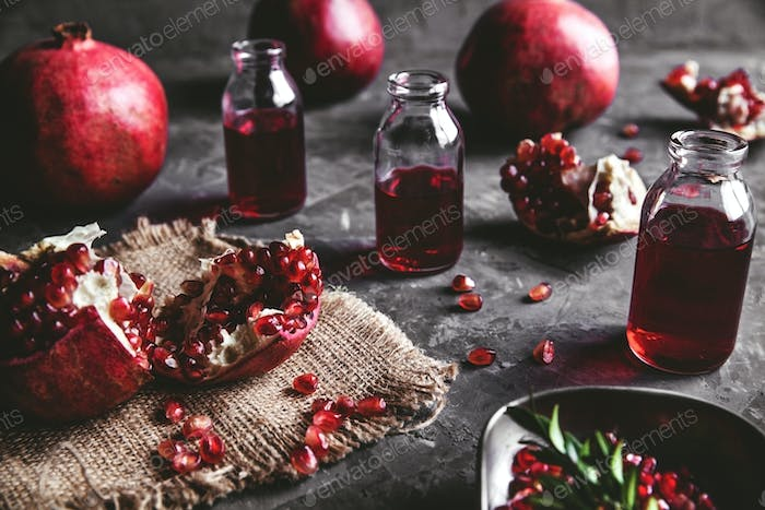 Wooden cutting board on grey background with pomegranate, healthy food, fruit