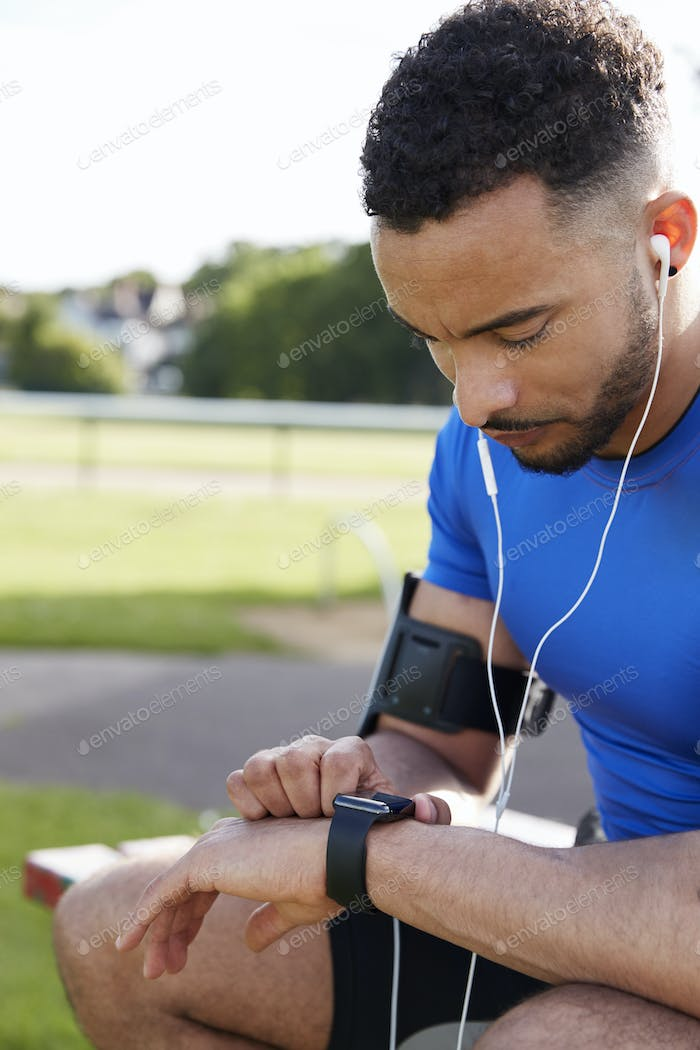 Young male athlete using fitness app on smartwatch, side view